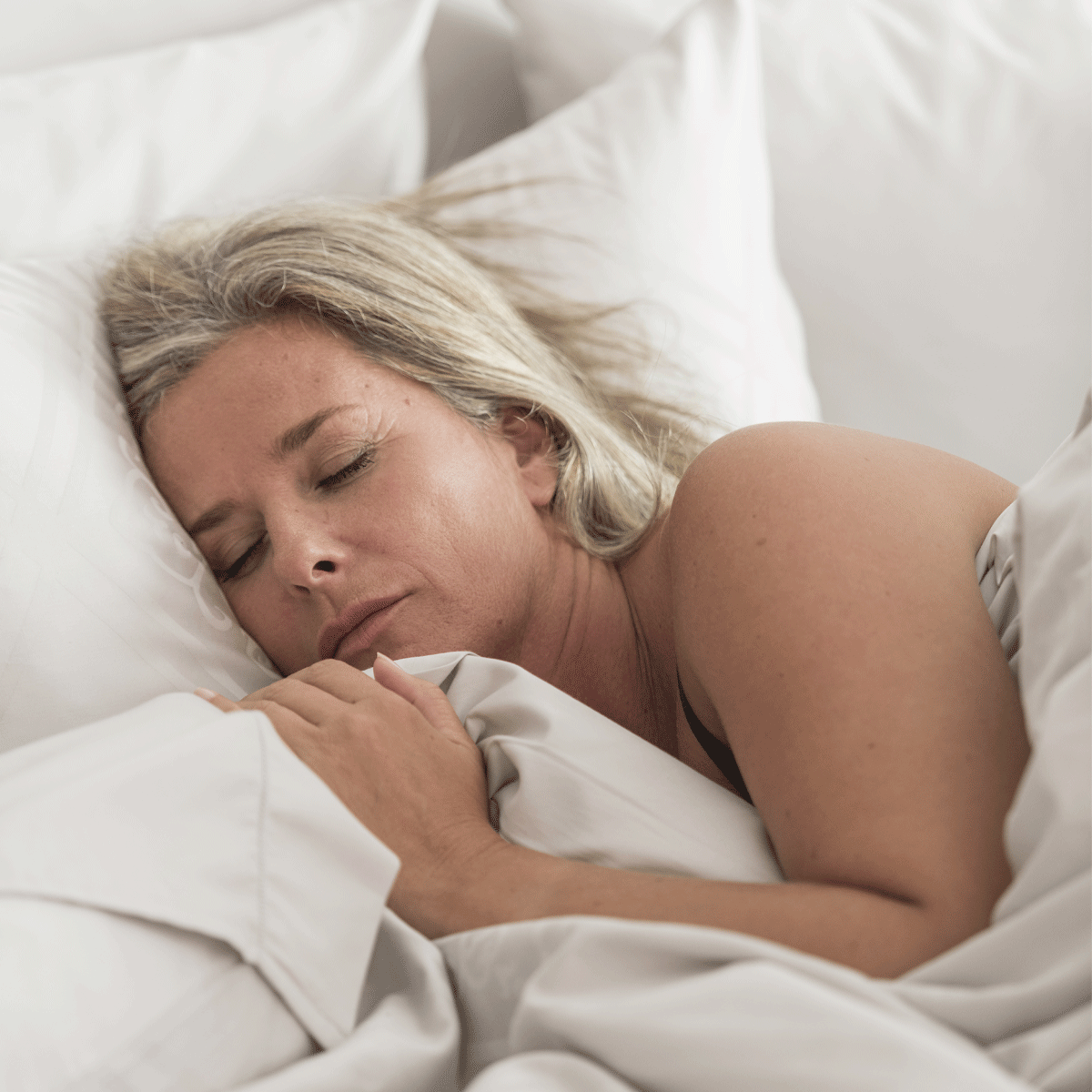 Woman sleeping in performance bed sheets